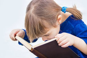 The child is reading a book. Selecti