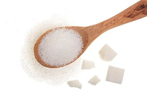 granulated sugar in wooden spoon with cube isolated on white background. Top view. Flat lay