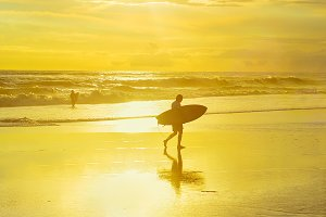 Surfer walking beach surfboard sun