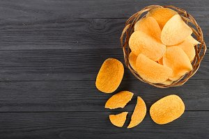 heap of potato chips in wicker basket on black wooden background with copy space for your text