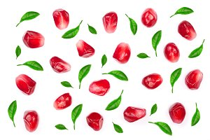 pomegranate seeds decorated with green leaves isolated on white background. Top view. Flat lay pattern
