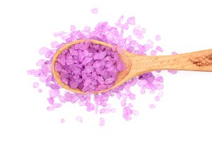 Violet sea salt in wooden spoon isolated on white background, lavender. Top view. Flat lay