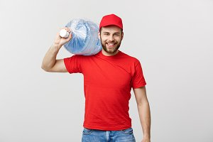Delivery Concept: Portrait of smiling bottled water delivery courier in red t-shirt and cap carrying tank of fresh drink isolated over grey background