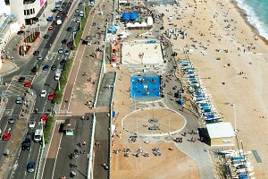 Aerial view of Brighton, people play basketball on court , parking for yachts