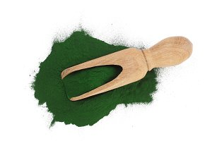 Spirulina algae powder in wooden scoop isolated on white background. Top view
