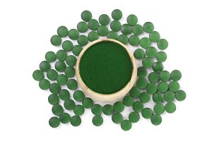 Spirulina algae powder and pills in wooden bowl isolated on white background. Top view