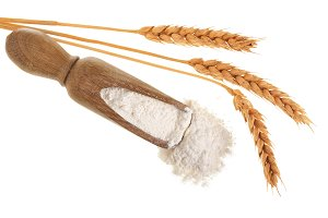 ears of wheat and pile of flour in wooden scoop isolated on white background. Top view. Flat lay