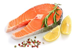 Slice of red fish salmon with lemon, rosemary and peppercorns isolated on white background