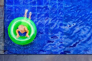 Child on ring in swimming pool