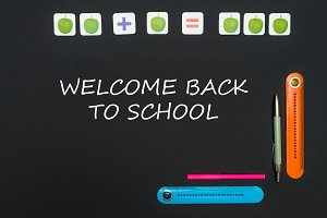 Black art table with stationery supplies with text welcome back to school on blackboard