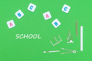 text school, from above wooden minitures school supplies and abc letters on green background
