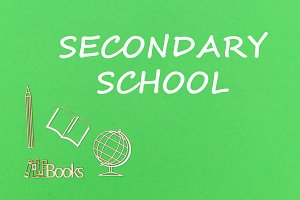 text secondary school, school supplies wooden miniatures on green background