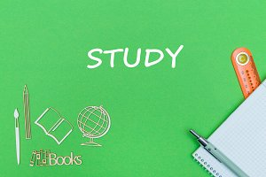 text study, school supplies wooden miniatures, notebook on green background