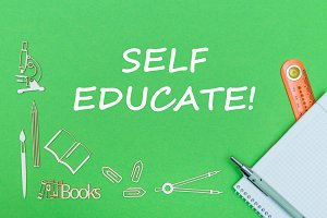 text self educate, school supplies wooden miniatures, notebook with ruler, pen on green backboard