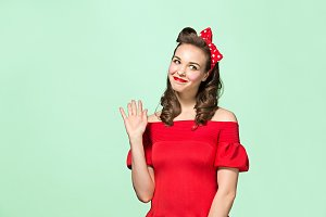 Beautiful young woman with pinup make-up and hairstyle. Studio shot on white background