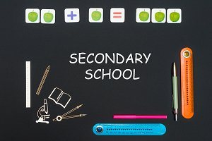 Above stationery supplies and text secondary school on blackboard