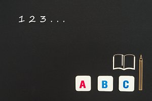 abc letters and chipboard miniature on blackboard with numbers 123