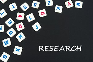 english colored square letters scattered on black background with text research
