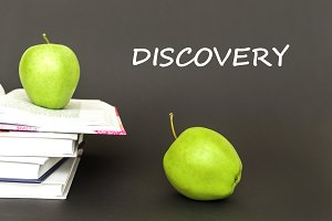 text discovery, two green apples, open books with concept