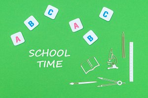 text school time, from above wooden minitures school supplies and abc letters on green background
