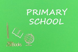 text primary school, school supplies wooden miniatures on green background