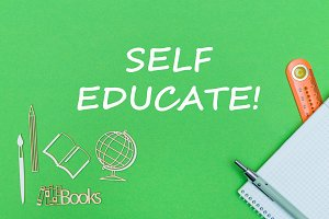 text self educate, school supplies wooden miniatures, notebook on green background