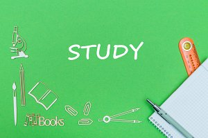 text study, school supplies wooden miniatures, notebook with ruler, pen on green backboard