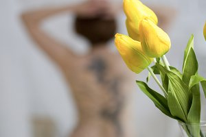 Yellow flowers in front of nude female model in a studio