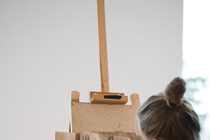 Rear view of female painter draws on the easel human figure