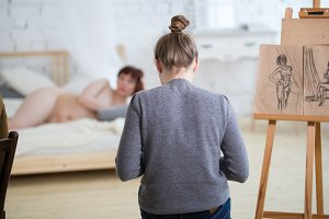 Rear view of female artist sketching of nude model in drawing class