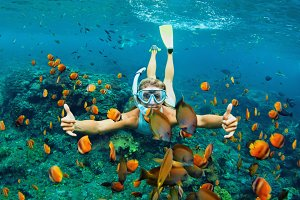 Young woman snorkeling at coral reef