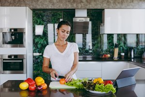A young woman cuts vegetables in the kitchen with a knife and laptop on the table. Vegetable salad. Dieting concept. Healthy lifestyle. Cooking at home. Prepare food. With place for text