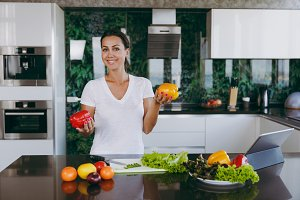 Young happy woman holding vegetables in hands in kitchen with laptop on the table. Vegetable salad. Dieting concept. Healthy lifestyle. Cooking at home. Prepare food. With place for text.