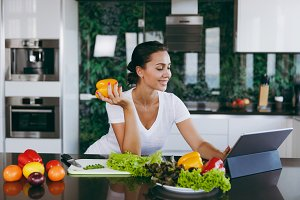 Young woman looking at recipe in laptop in kitchen. Healthy food - Vegetable salad. Dieting concept. Healthy lifestyle. Cooking at home. Prepare food. With place for text.