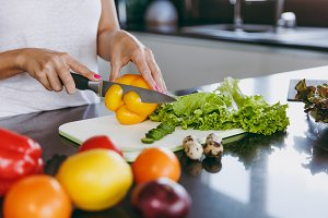 A young woman cuts vegetables in the kitchen with a knife. Healthy food - Vegetable salad. Dieting concept. Healthy lifestyle. Cooking at home. Prepare food Close up