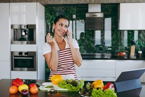 Young happy woman in apron talking on mobile phone in kitchen with laptop on the table. Vegetable salad. Dieting concept. Healthy lifestyle. Cooking at home. Prepare food.