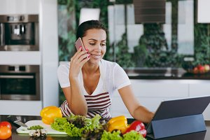 Young happy woman in apron talking on mobile phone and looking at recipe in laptop in the kitchen. Vegetable salad. Dieting concept. Healthy lifestyle. Cooking at home. Prepare food.