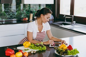 Young happy woman in apron looking at recipe in tablet in the kitchen. Vegetable salad. Dieting concept. Healthy lifestyle. Cooking at home. Prepare food.