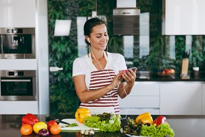 Young happy woman with headphones in the ears holding mobile phone in hands in kitchen. Vegetable salad. Dieting concept. Healthy lifestyle. Cooking at home. Prepare food