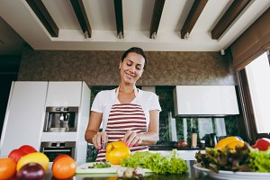 A young woman cuts vegetables in the kitchen with a knife. Healthy food - Vegetable salad. Dieting concept. Healthy lifestyle. Cooking at home. Prepare food