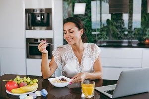 Portrait of beautiful happy woman working with laptop while breakfast with cereals and milk. Eating at home.