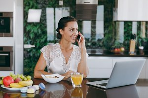 Portrait of beautiful happy woman talking on a mobile phone while breakfast with laptop on the table. Eating at home.