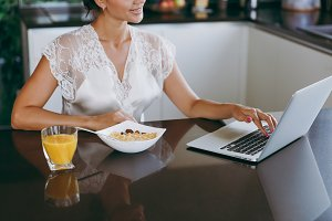 Portrait of beautiful young woman working with laptop while breakfast with cereals and milk. Eating at home.