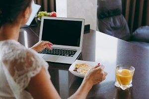Young woman working with laptop while breakfast with cereals and milk. Eating at home close up. Back view. With place for text.