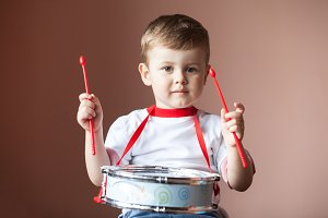 Little boy playing the drum. Child development concept.
