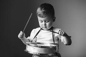 Little boy playing the drum. Child development concept.