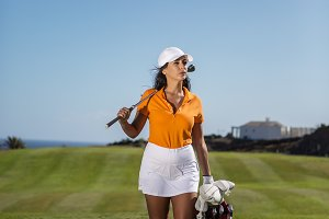 Stylish woman with golf drivers on f