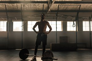 Muscular man with barbell standing