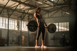 Cross fit woman lifting heavy weight