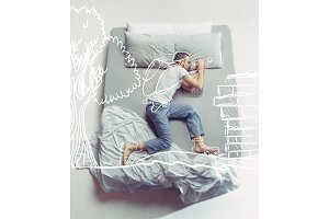 Top view photo of young man sleeping in a big white bed and his dreams